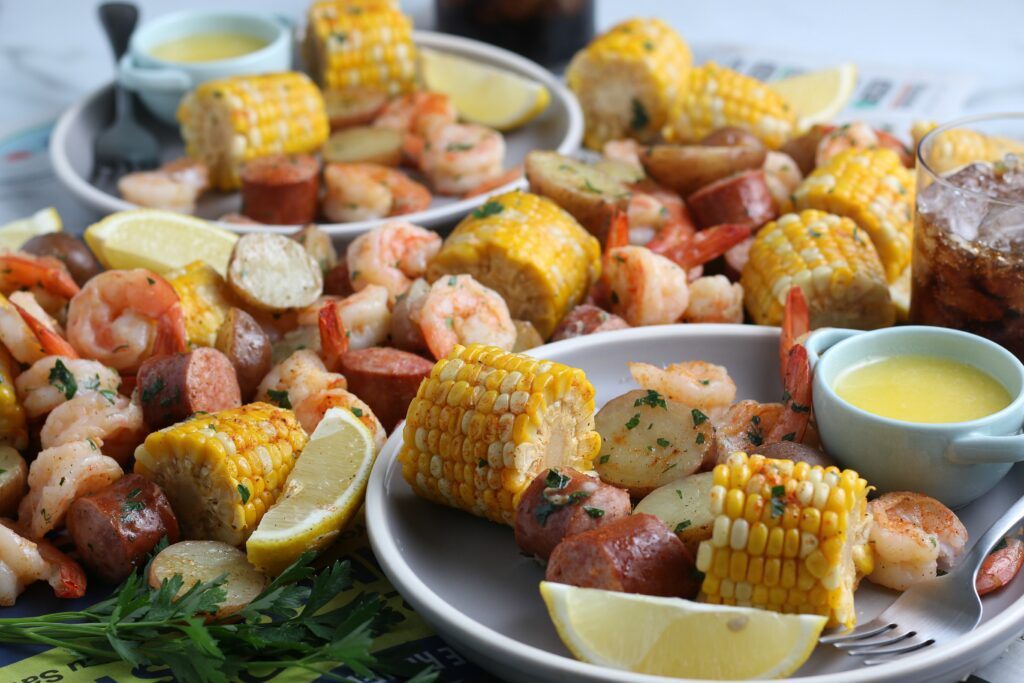 Shrimp boil made with corn, potatoes and sausage, and served with butter and lemons on a white plate