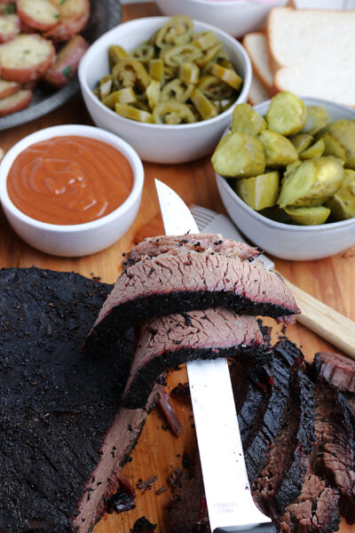 cooked smoked brisket, slice laying over knife, served with condiments
