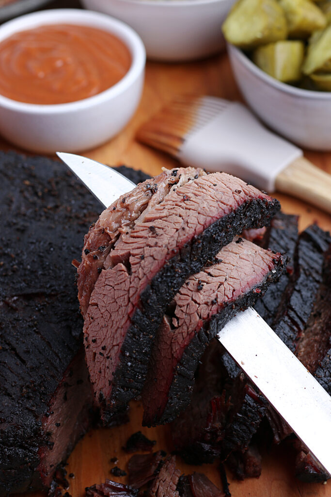 smoked brisket being served over knife with pickles and barbecue sauce