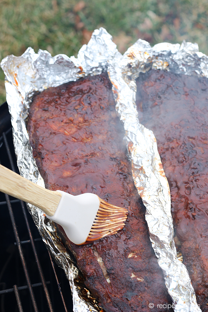 Smothering smoked ribs with BBQ sauce