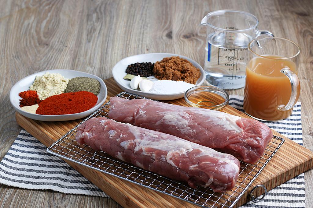 seasonings (rubs) and uncooked pork tenderloin displayed on cutting board