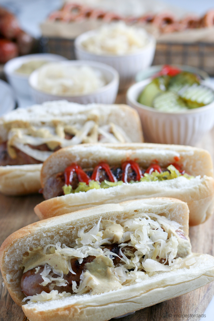 Grilled Beer Brats served with sauerkraut and mustard, with a red and white checkered napkin