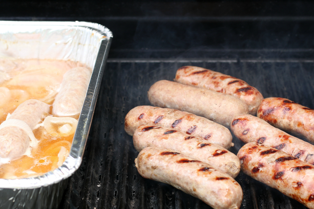 eight brats being grilled, along with beer and onions
