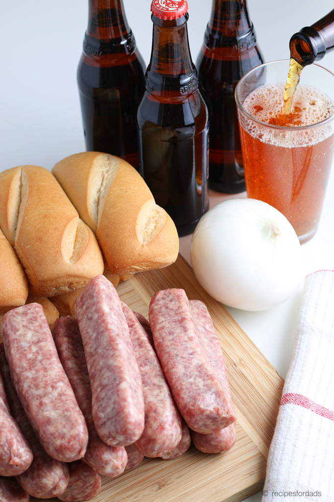 Beer, Hoagie buns, uncooked brats and onion served on cutting board
