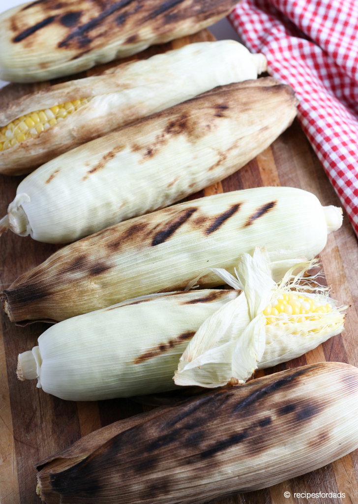 Corn on the cob with husks on, served on cutting board with a red and white checkered napkin