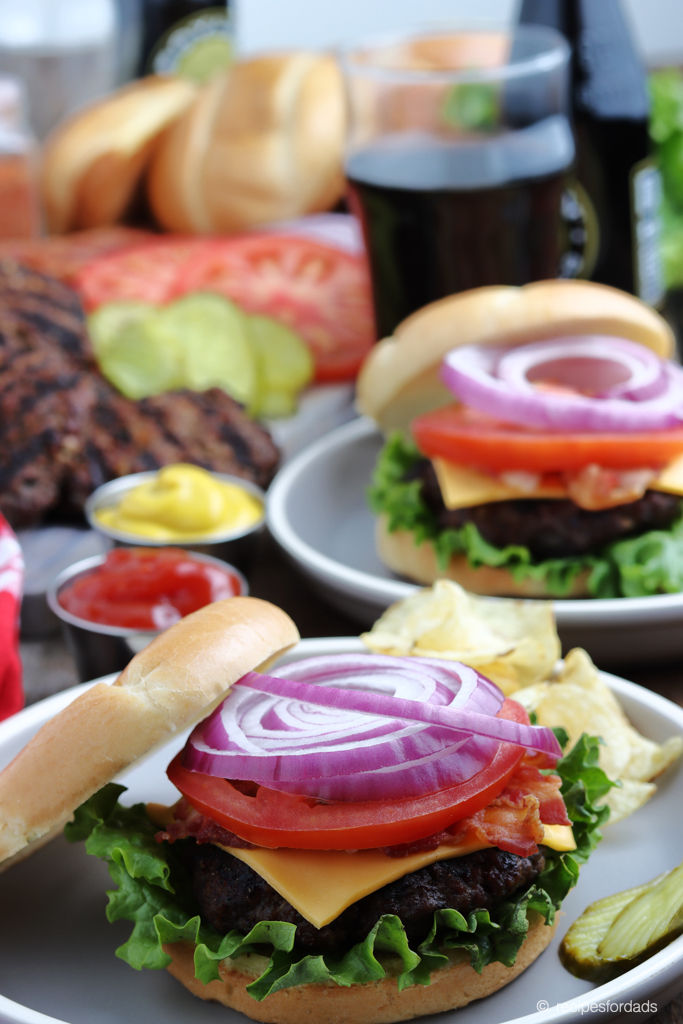 Grilled Burgers topped with lettuce, tomatoes, onion and cheese