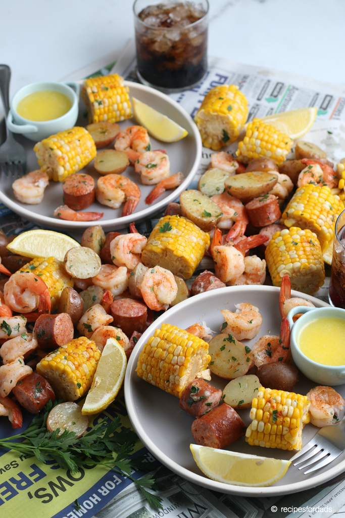 Shrimp boil made with corn, potatoes and sausage, and served with butter and lemons