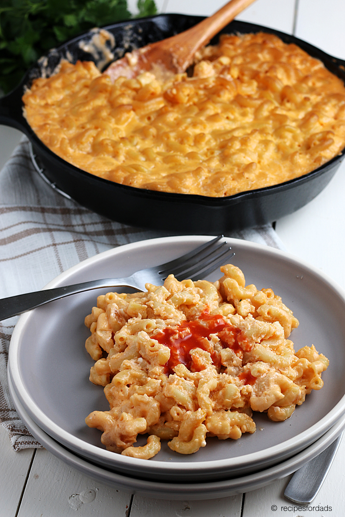 Smoked mac and cheese in a cast iron skillet served with hot sauce on top