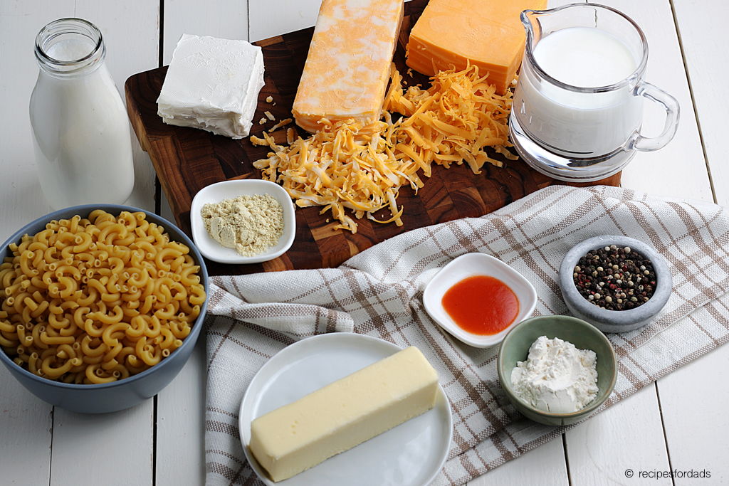seasonings and ingredients used with  homemade macaroni and cheese, served on a white board