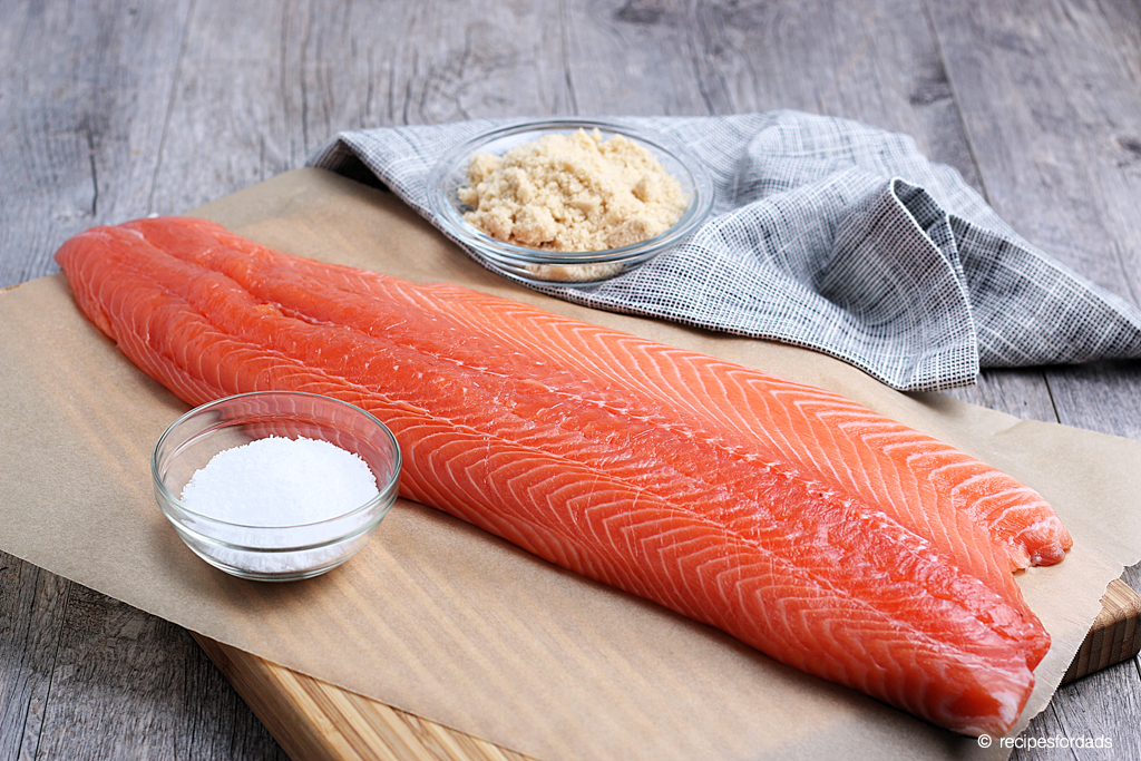 Preparing wild salmon with salt and brown sugar for the smoker, served on white board and napkin