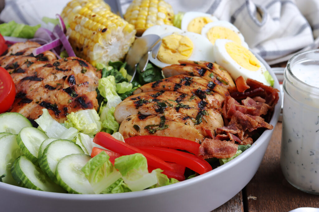 delicious grilled chicken cobb salad served with corn on the cob and boiled eggs.