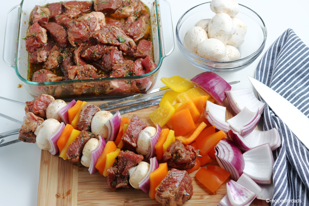 beef kabobs marinating with vegetables chopped on serving board