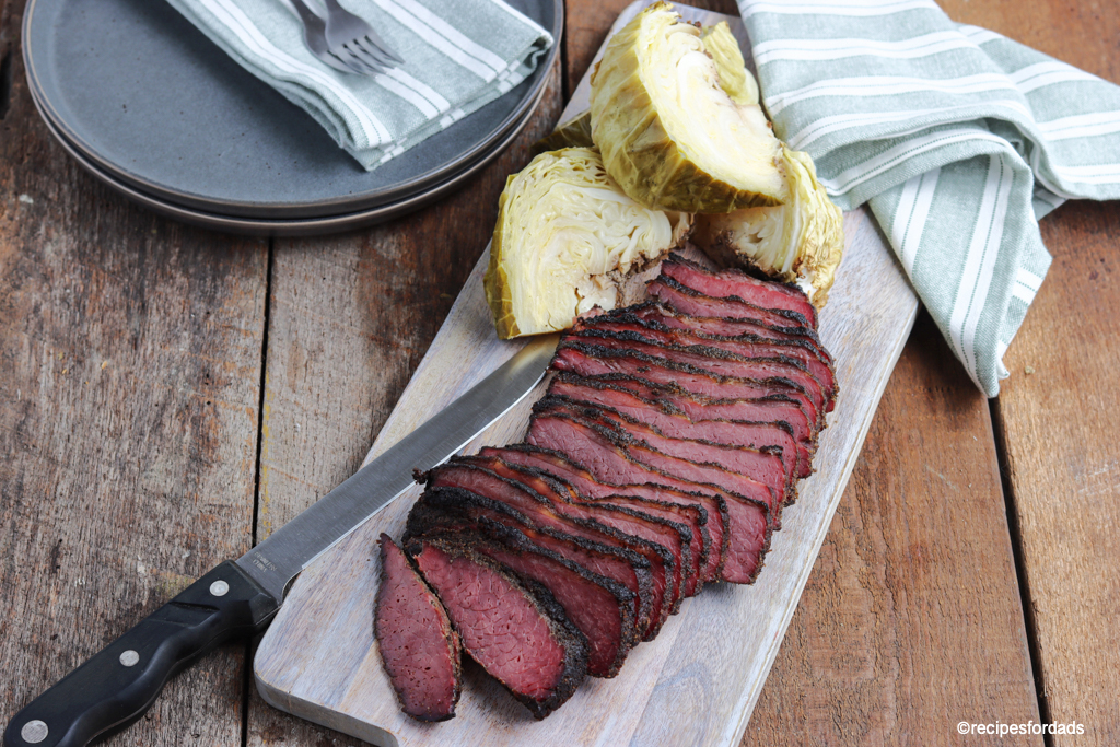 sliced brisket and sliced cabbage served on cutting board