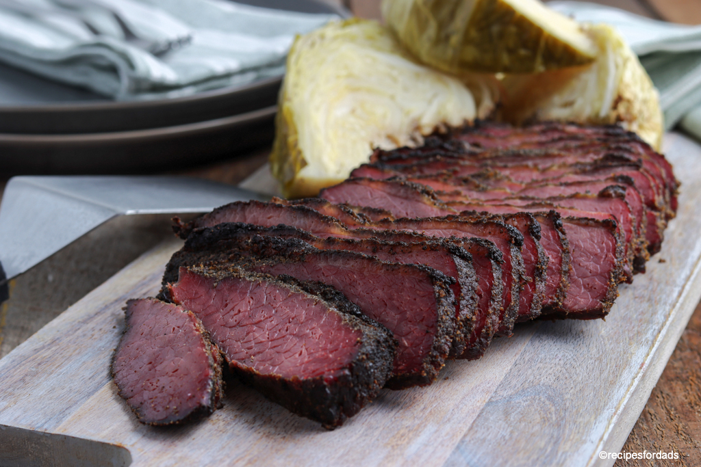 Smoked corned beef and cabbage sliced and served on cutting board