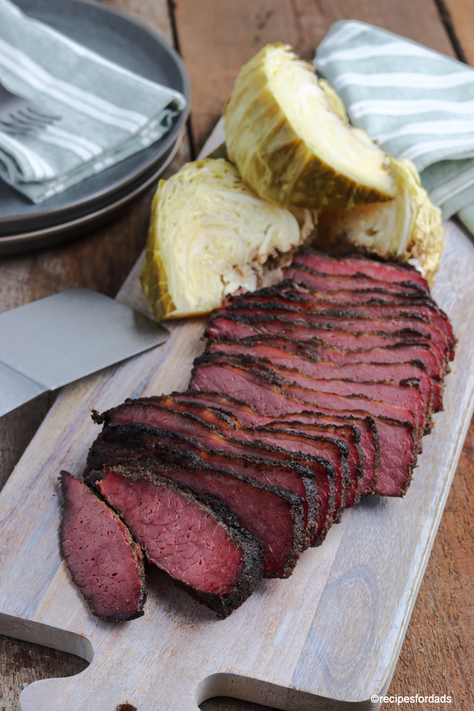 sliced smoked corned beef and cabbage served on cutting board