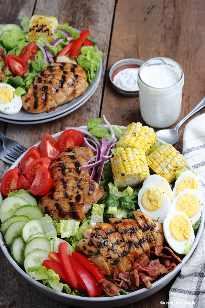 delicious grilled chicken cobb salad served with corn on the cob and boiled eggs, paired with ranch dressing
