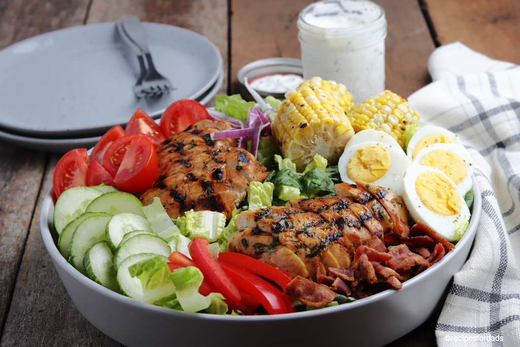 delicious grilled chicken cobb salad served with corn on the cob and boiled eggs (in a gray serving bowl)