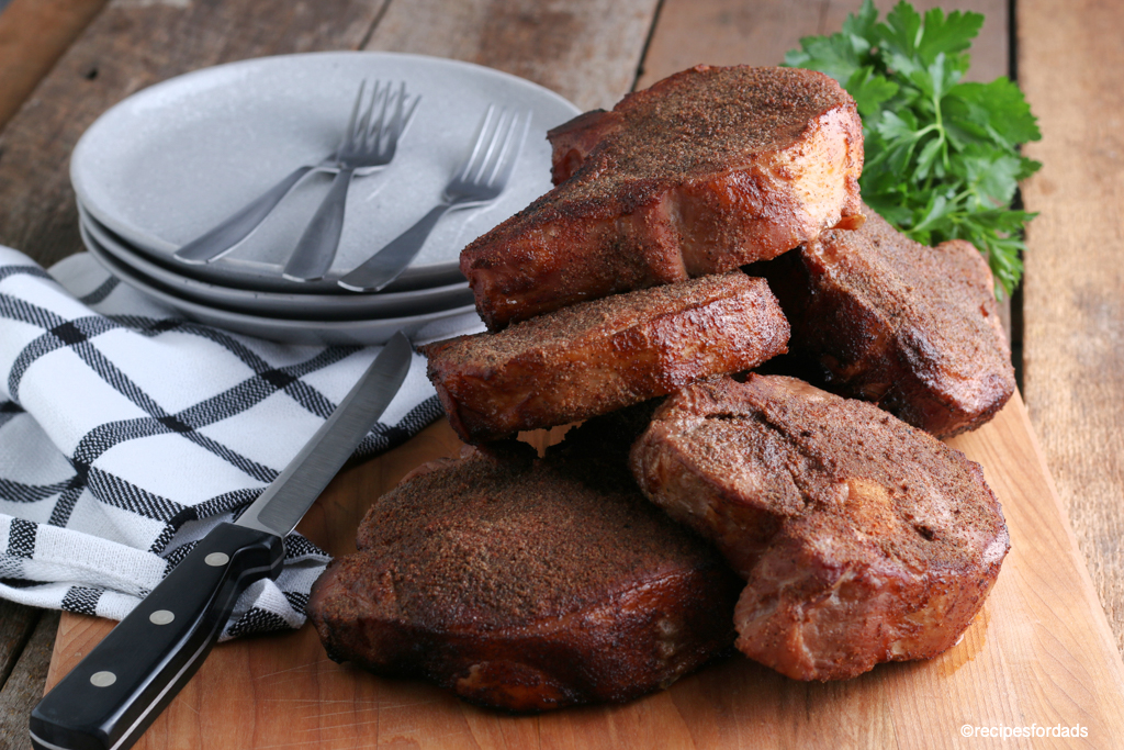 Six smoked pork chops displayed on cutting board with black and white napkin