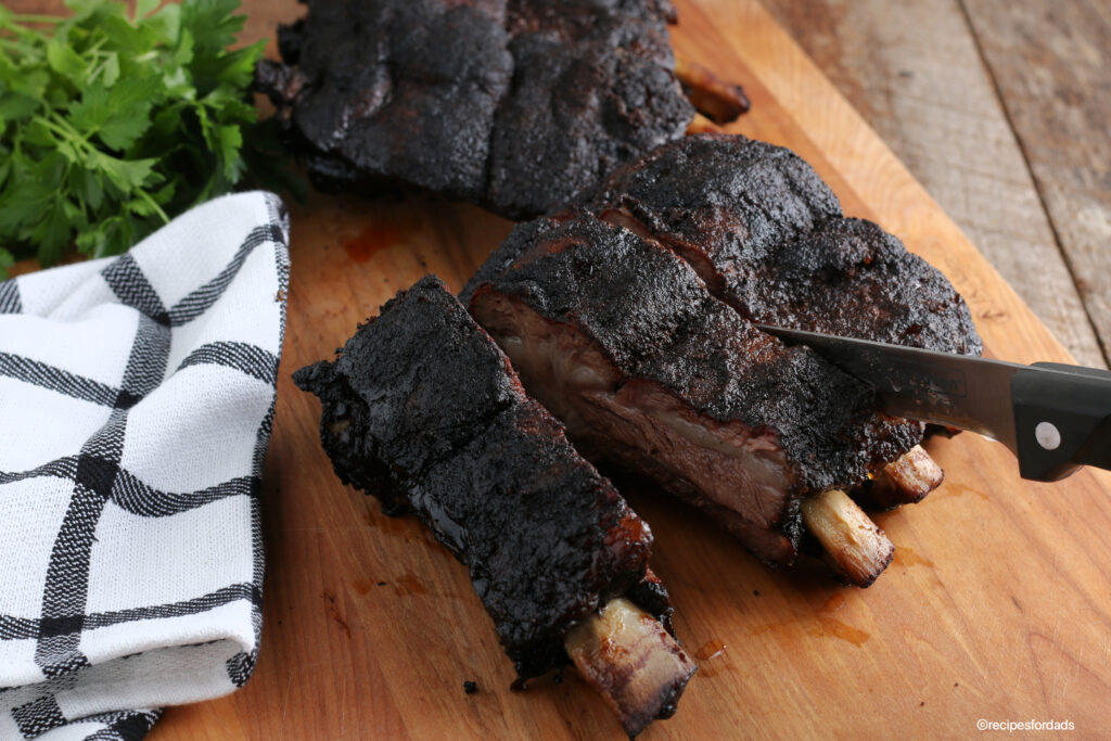 Cutting beef ribs on cutting board with knife and black & white napkin