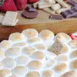 s'mores dip served with strawberries and graham crackers