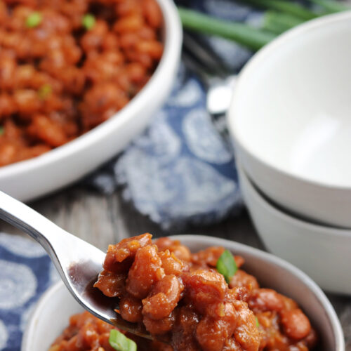 baked beans served in white bowl, with pressure cooker in the background