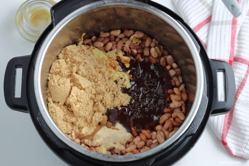 ingredients mixed together to make bbq baked beans in a pressure cooker
